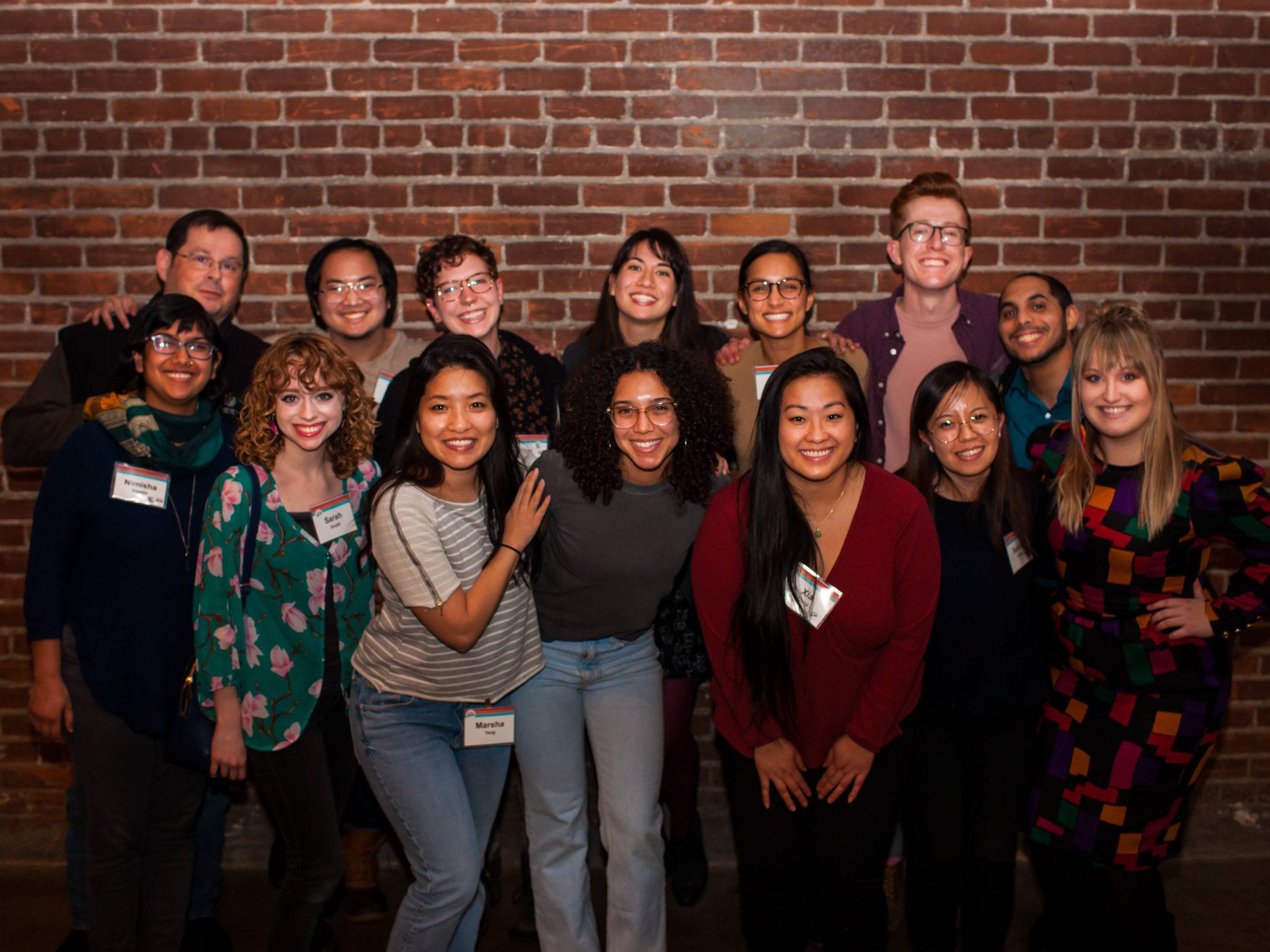 14 people of diverse background pose for a photo against a brick wall.
