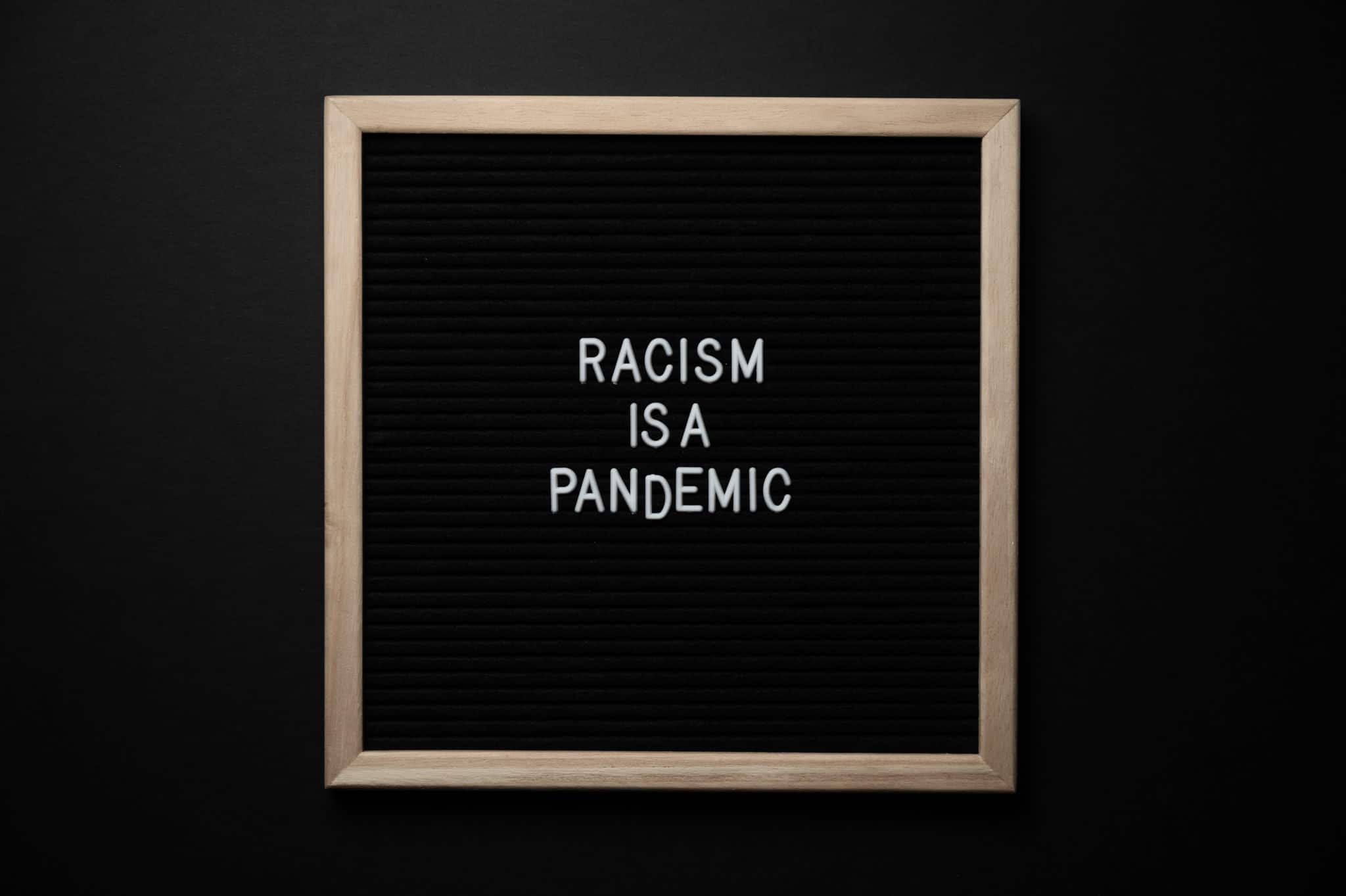"White letters against a black backdrop spell out the words ""Racism is a pandemic"""