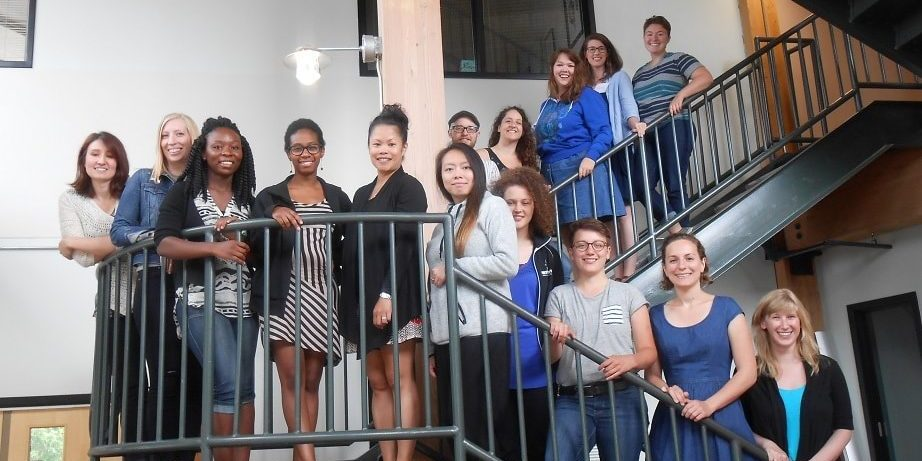 15 people of diverse backgrounds stand together along a multi-level staircase, smiling for a group photo.